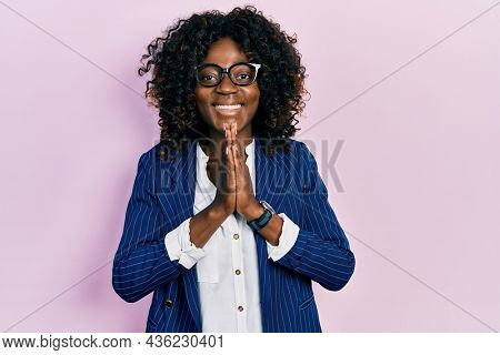 Young african american woman wearing business clothes and glasses praying with hands together asking for forgiveness smiling confident.