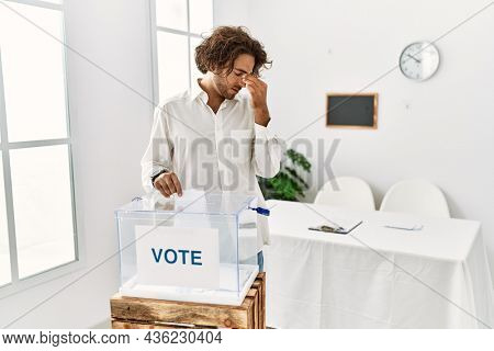 Young hispanic man voting putting envelop in ballot box tired rubbing nose and eyes feeling fatigue and headache. stress and frustration concept.