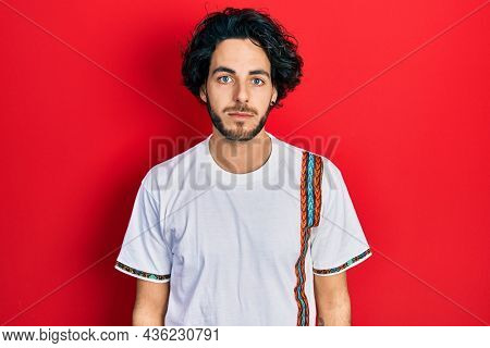 Handsome hispanic man wearing casual white t shirt with serious expression on face. simple and natural looking at the camera.