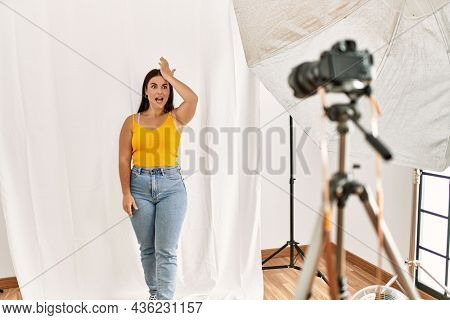 Young beautiful hispanic woman posing as model at photography studio surprised with hand on head for mistake, remember error. forgot, bad memory concept.