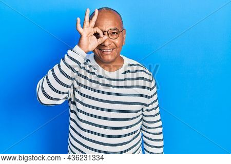 Middle age latin man wearing casual clothes and glasses doing ok gesture with hand smiling, eye looking through fingers with happy face.