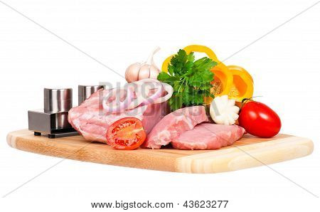 Raw pork with vegetables on a cutting board isolated over white background poster