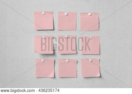 Blank pink note papers, memos on gray wall