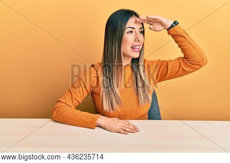 Young hispanic woman wearing casual clothes sitting on the table very happy and smiling looking far away with hand over head. searching concept.