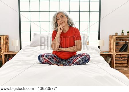 Middle age woman with grey hair sitting on the bed at home with hand on chin thinking about question, pensive expression. smiling with thoughtful face. doubt concept.