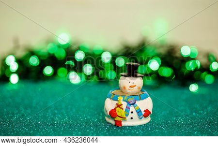 Small Snowman Toy In Front Of Defocused Xmas Lights. Holiday Card. Christmas Card Decorated With Bok