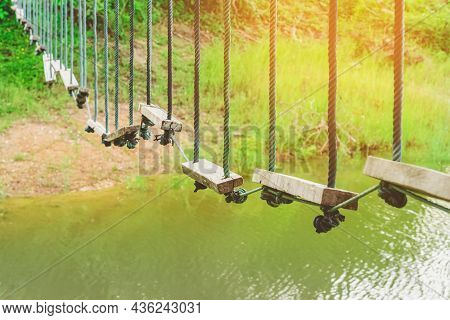 Many Swings Made Of Wooden Board And Tied With Rope Hang On Cable Over A Small Stream Flowing Throug