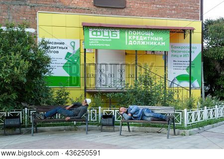 Irkutsk, Russia - July 26, 2021 Homeless People Sleep On A Bench Near A Bankruptcy Aid Law Firm.