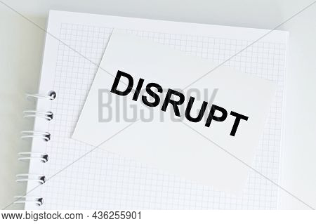 Disrupt Text On White Card On The Background Of A White Notebook, Top View