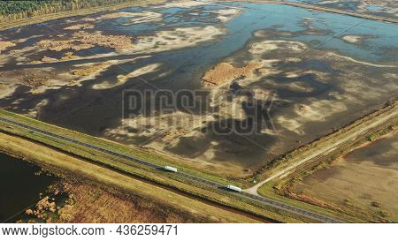 Aerial View Of Highway Road Through Ponds Autumn Landscape. Two Trucks Tractors Units Prime Movers T