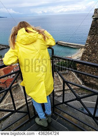 A Girl In A Bright Yellow Raincoat Looks At The Observation Deck In The City Of Pizzo, Italy And Loo