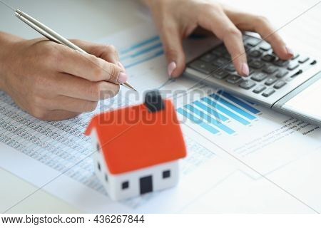 Woman Makes Calculations On Calculator For Buying House On Credit