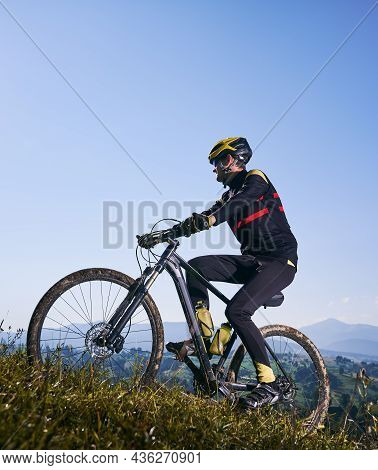Sportsman In Safety Helmet And Glasses Cycling Uphill On Sunny Day With Blue Sky On Background. Bicy