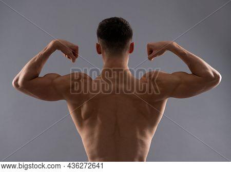 Fit Man Rear Torso Flex Arm Muscle Showing Biceps Triceps Grey Background, Flexing