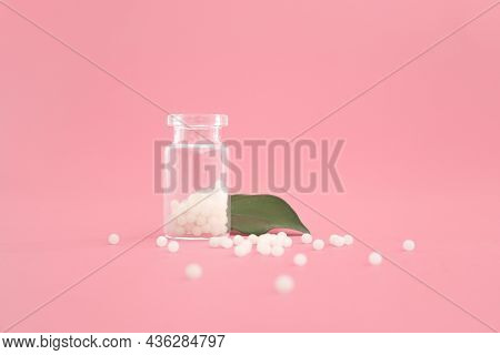 Close-up Image Of Homeopathic Globules In Glass Bottle On Pastel Pink Background. Homeopathy Pharmac