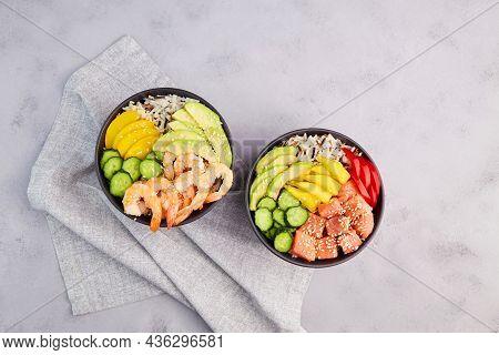 Poke Bowl With Shrimps, Salmon, Avocado, Rice, Cucumber, Mango, Pepper And Sesame Seeds On Grey Back