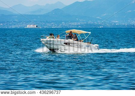 Bardolino, Italy - May 26, 2021: Small Rental Motorboat With A Family On Board In Motion On Lake Gar