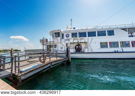 Bardolino, Italy - May 26, 2021: White Ferry Boat Is Arriving At Ferry Station Of The Small Bardolin