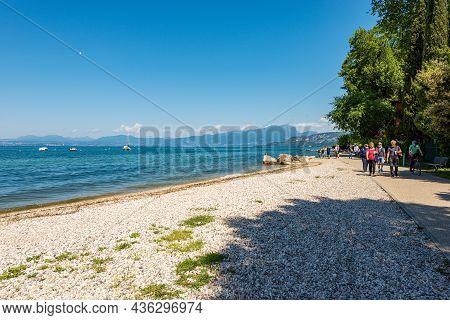 Bardolino, Italy - May 26, 2021: Coast Of Lake Garda With A Beach And Bicycle And Pedestrian Lane Th