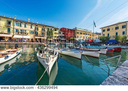 Lazise, Italy - May 26, 2021: Port With Small Boats Moored Of The Small Lazise Village, Tourist Reso
