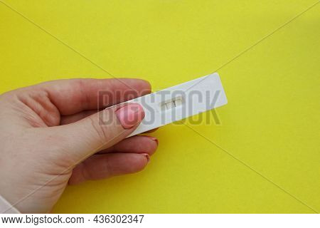 A Woman Is Hand Holding A Positive Pregnancy Test On A Yellow Background. Motherhood, Pregnancy, Hap