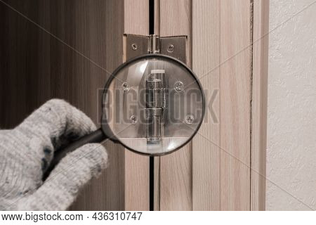 The Hand Of A Male Worker In A Construction Glove Examines Through A Magnifying Glass The Door Hinge