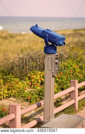 A Pair Of Binoculars, Telescope Stands Above A Beach To Observe The Sea.