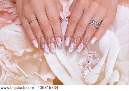 Female Hands With Ombre Manicure Nails, Pink Gel Polish, On Paper Flowers Background