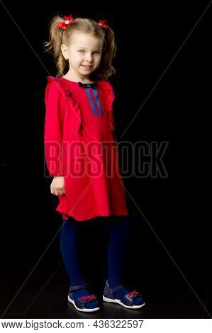 Cute Blonde Little Girl Standing On Black Backdrop. Charming Smiling Girl With Cute Ponytails Hairst