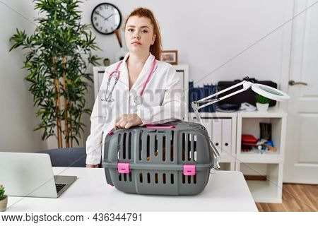 Young redhead veterinarian woman working at pet clinic thinking attitude and sober expression looking self confident