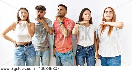 Group of young friends standing together over isolated background cutting throat with hand as knife, threaten aggression with furious violence
