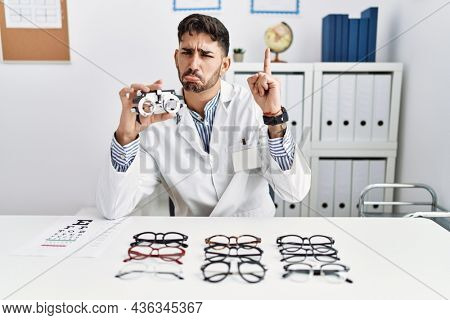 Young optician man holding optometry glasses pointing up looking sad and upset, indicating direction with fingers, unhappy and depressed.