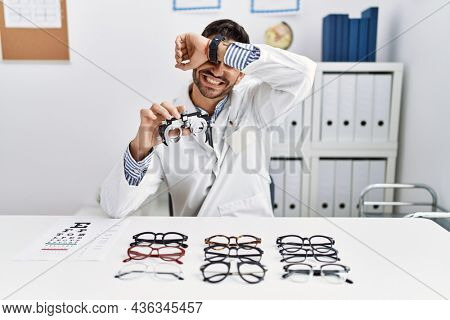 Young optician man holding optometry glasses smiling cheerful playing peek a boo with hands showing face. surprised and exited