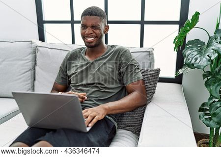 Young african american man using laptop at home sitting on the sofa winking looking at the camera with sexy expression, cheerful and happy face.