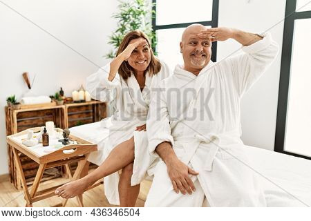 Middle age hispanic couple wearing bathrobe at wellness spa very happy and smiling looking far away with hand over head. searching concept.
