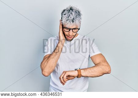 Young hispanic man with modern dyed hair wearing white t shirt and glasses looking at the watch time worried, afraid of getting late