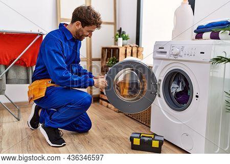 Young hispanic man wearing handyman uniform repairing washing machine at laundry room
