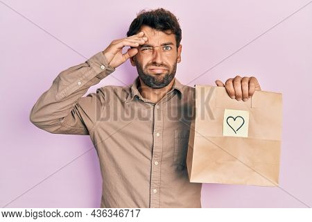 Handsome man with beard holding delivery paper bag with heart reminder worried and stressed about a problem with hand on forehead, nervous and anxious for crisis