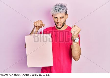 Young hispanic man with modern dyed hair holding shopping bag annoyed and frustrated shouting with anger, yelling crazy with anger and hand raised