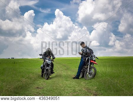 Two Men With Their Motorcycles Parked Chatting In The Field, Two Young Motorcyclists In The Field, T
