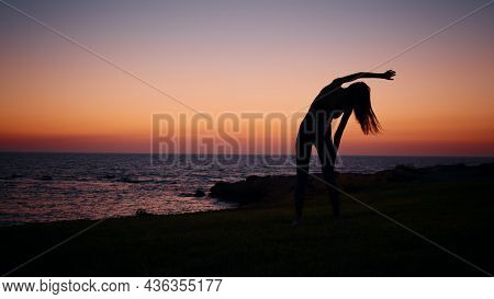 Young Woman With Slender Body Practising In Fitness Exercises During Evening Time Near Ocean. Silhou