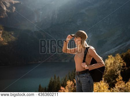 Wanderlust And Travel Concept. Stylish Traveler Girl In Cap Looking In Front Of Mountain On Sunny Da