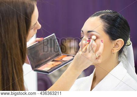 Makeup Artist Applies Makeup To Beautiful Young Girl Holding Set Of Cosmetics