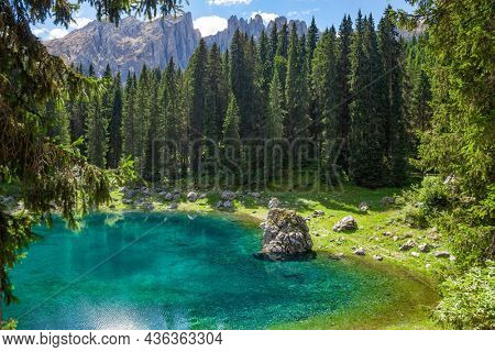 Turquoise colored alpine lake Carezza (Karersee), a famous tourist destination in Bolzano province, South tyrol, Italy. Latemar mountain range of the Dolomites is seen in background