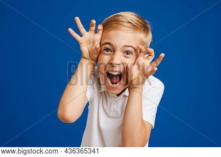 White blonde boy grimacing and gesturing while screaming at camera isolated over blue background
