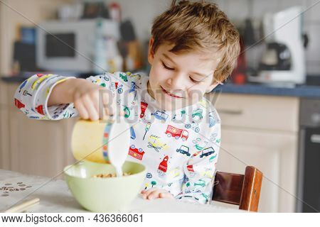 Happy Little Blond Kid Boy Eating Cereals For Breakfast Or Lunch. Healthy Eating For Children In The