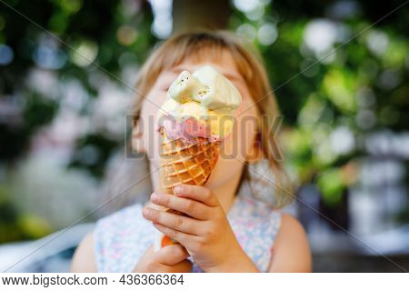 Little Preschool Girl Eating Ice Cream In Waffle Cone On Sunny Summer Day. Happy Toddler Child Eat I