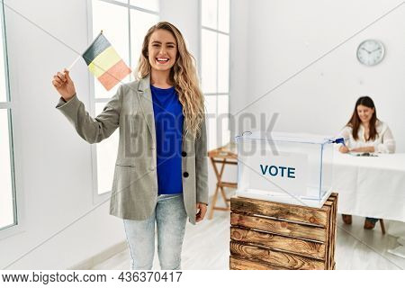 Young belgian voter woman smiling happy holding belgium flag at electoral college.