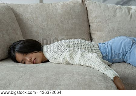 Exhausted Young Asian Woman Falls On The Sofa. A Tired, Lazy Woman Is Sleeping On The Couch At Home