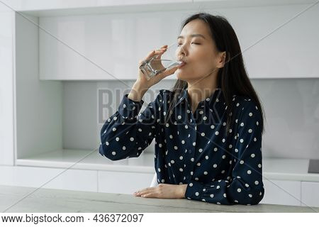 Young Asian Woman Drinks Water From A Glass Sitting In The Kitchen. A Young Woman Smiles While Holdi